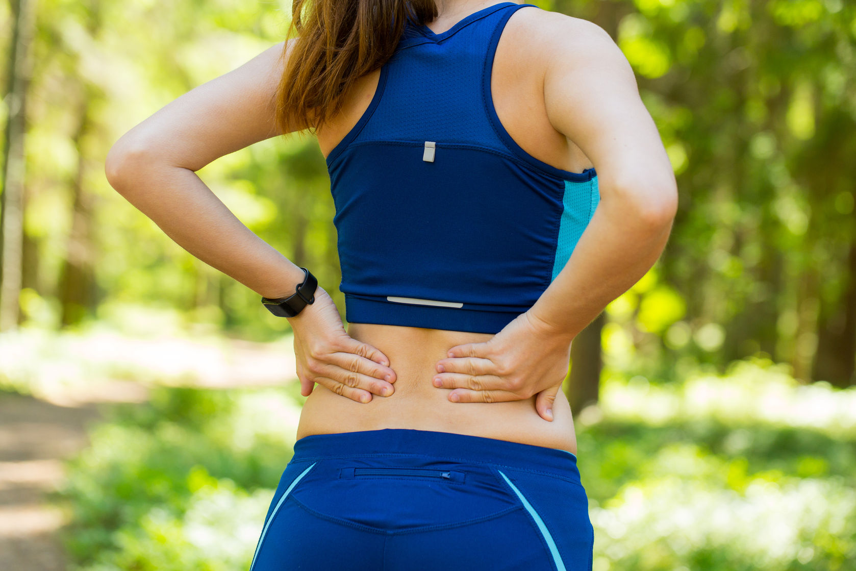 athletic woman holding her painful injured back