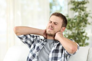 man suffering neck pain