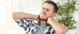 man suffering neck pain sitting on a sofa